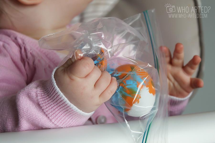 ребенок мнет пакет с яйцом и акриловыми красками