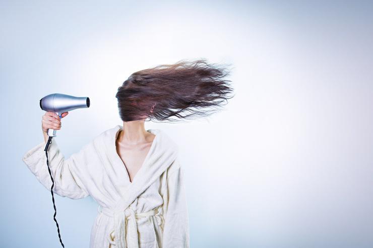 сушит волосы феном девушка