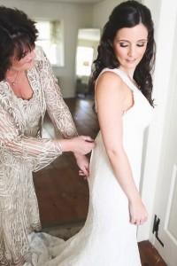 Мама застегивает свадебное платье